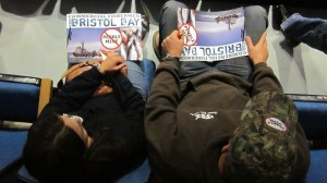 Two activists hold anti-Pebble Mine posters in a back row of the Wendy Williamson Auditorium during an EPA public comment meeting on the Draft Bristol Bay Watershed Assessment.