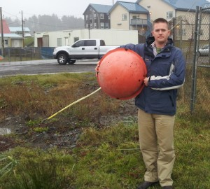 U.S. Coast Guard Lt. Lance Leone holds one of the warning balls on the power lines his helicopter hit on July 7, 2010. According to a Coast Guard memo after the crash, these warning balls are half as big as the ones normally used, were faded and required replacement, and according to earlier photos, were positioned over land, leaving a large portion of the lines unmarked. The memo also states FAA regulations don't require power lines as low as the ones in the accident to be marked. (Photo provided by Leone)