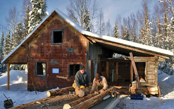 Volunteers Bill Nelson (left) and Bud Crawford unload logs in front of the Watchmen's Cabin, which is being restored at the Kasilof Regional Historical Association's museum. Photo courtesy Joseph Robertia, Redoubt Reporter.