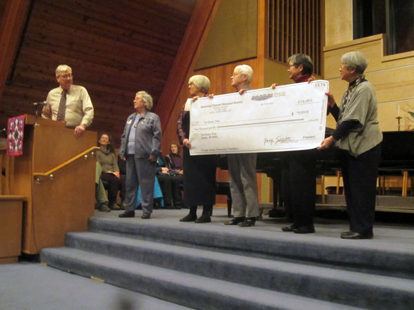 The Gastineau Channel Historical Society presents a $5,000 check to organizers of the Empty Chair project in Juneau. On the far right are sisters Mary Tanaka Abo and Alice Tanaka Hikido, whose brother John inspired the proposed memorial to Juneau's Japanese American internees. Photo by Casey Kelly/KTOO.