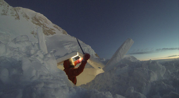 Lonnie building his snow shelter at 14.2K with Denali's summit ridge in the background. Photo courtesy of Lonnie Dupre.