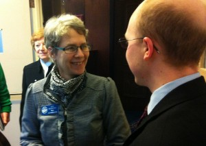 Sitka Mayor Mim McConnell runs into state Rep. Jonathan Kreiss-Tomkins (D-Sitka) in the main stairwell at the Alaska Capitol on Thursday morning. In the background is Marlene Campbell, the city's government relations director. (KCAW photo by Ed Ronco)