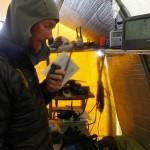 Denali mountaineering ranger David Weber on the radio phone at the Kahiltna Basecamp. NPS Photo/Menno Boermans.
