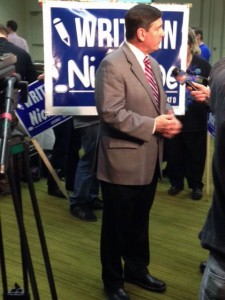 Anchorage Mayor Dan Sullivan stands in front of a 'Write in Nick Moe' campaign sign at Dena'ina Center where he talked with TV reporters about election results. Photo by Daysha Eaton, KSKA - Anchorage.