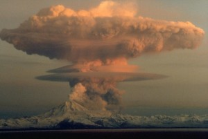 Ascending eruption cloud from Redoubt Volcano as viewed to the west from the Kenai Peninsula. The mushroom-shaped plume rose from avalanches of hot debris (pyroclastic flows) that cascaded down the north flank of the volcano. A smaller, white steam plume rises from the summit crater. Photograph by R. Clucas, April 21, 1990.