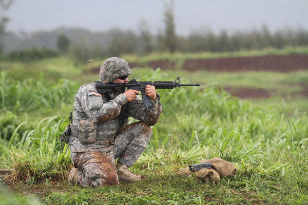 Sgt. Daniel S. Alsdorf fires his M4 carbine from a kneeling position during the weapons qualification event as part of the Pacific Army Reserve Best Warrior Competition, May 18. May 19. Photo by Army Staff Sgt. Joseph Vine.