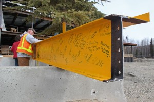 People signed the final piece of steel before it was hoisted into place. Photo by Josh Edge, APRN - Anchorage.