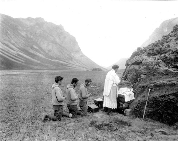 "Father Hubbard entitled this image ""Mass in a Volcano Crater."" Hubbard began every day with Mass, no matter where he found himself. This photo of Hubbard and his party is taken during Hubbard's two-month exploartion of the Aniakchak Crater on the Alaskan Peninsula, not long after Aniakchak's May 12, 1931 eruption. Hubbard's account and photos of this expedition were published in magazines and newspapers across Amnerica. (Left to right: William Regan, Richard Doublas, Kenneth Chisolm, Bernard Hubbard) Photo taken in 1931 by unnamed member of Hubbard's party. Courtesy of Santa Clara University."