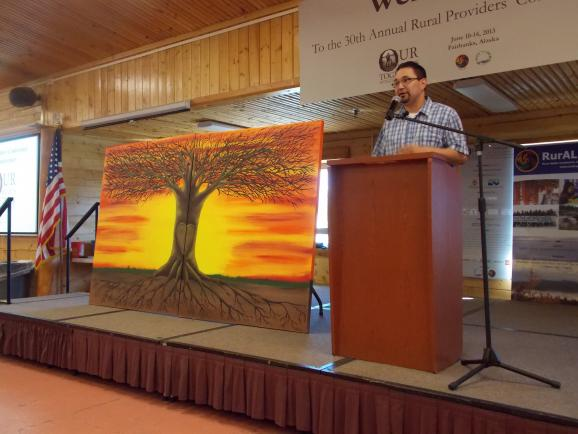 Travis Cole and his tree painting. Credit Dan Bross / KUAC