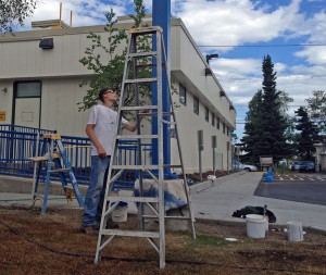 A worker paints outside at the redesigned Access Alaska Building. Photo by Daysha Eaton, KSKA - Anchorage.