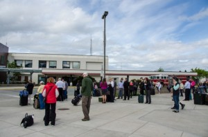 Dozens of people and their luggage waiting in the parking lot. (Photo by Heather Bryant/KTOO)