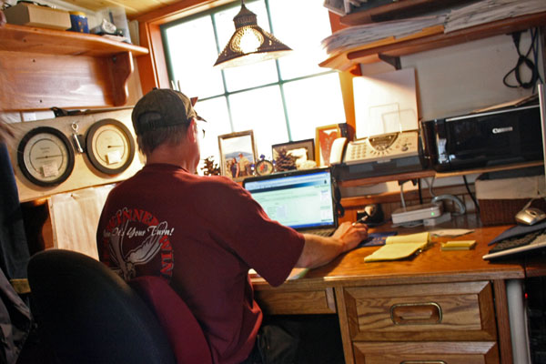 Bill Luedke sends weather data to Juneau from a desk in his Port Alexander home. Next to him are two barometers and, on the shelfs above, hundreds of sheets of handwritten weather data from the last few years. (KCAW photo by Ed Ronco)