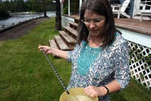 Kim Luedke shows the rain gauge in her yard. In the 24 hours before this photo was taken, Port Alexander recorded 0.02 inches of rainfall. Luedke and her husband Bill are paid weather observers in the small Baranof Island community. Their data is used by the National Weather Service and the FAA. (KCAW photo by Ed Ronco)