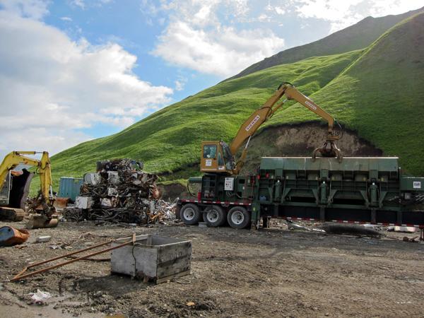 Crushed scrap sits next to Ron Moore's metal compactor. (Audrey Carlsen/KUCB)