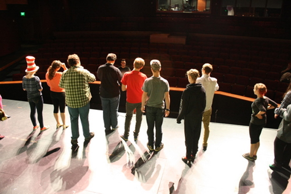 "Cast members gather at the edge of the stage to talk with director WT McRae and musical director Andrew Hames, during a rehearsal of ""Seussical the Musical"" Wednesday at the Sitka Performing Arts Center. The full-scale musical will open Friday night after just two weeks of rehearsal. (KCAW photo by Ed Ronco)"