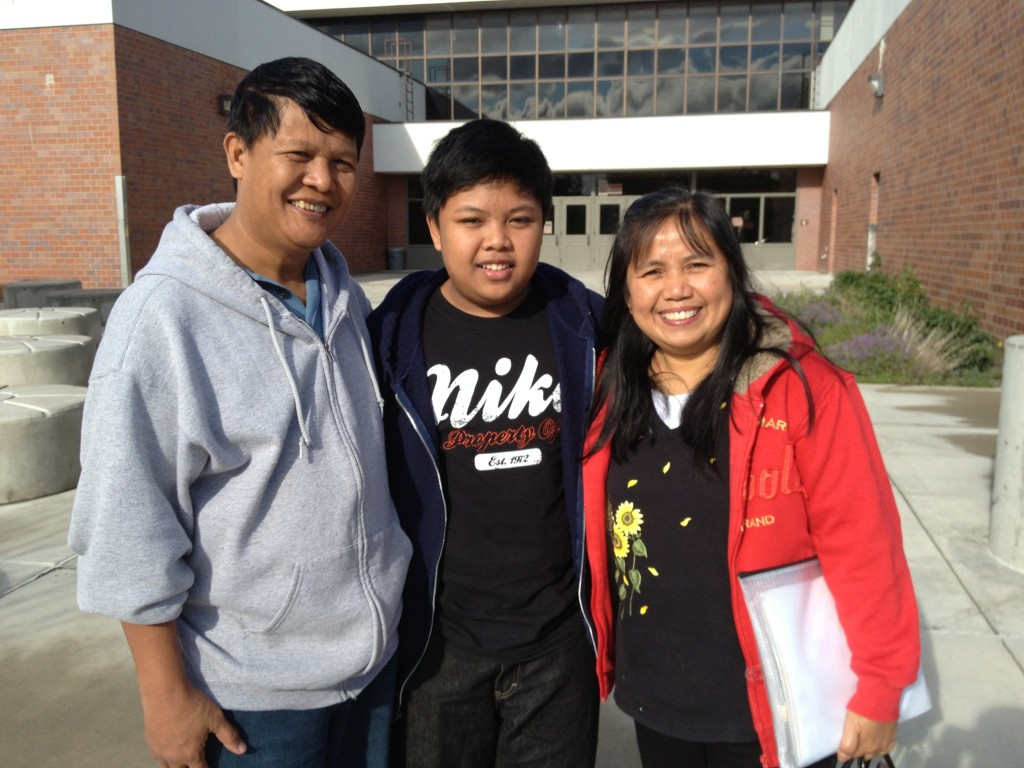 8th Grader Nester Cunanan III stands in front of Mears Middle School in South Anchorage with his mother, Natalia Cunanan and his father Nester Cunanan Jr.