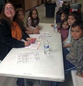 Tabytha Gardner fills out paperwork, registering her children for school. Photo by Daysha Eaton, KSKA - Anchorage.