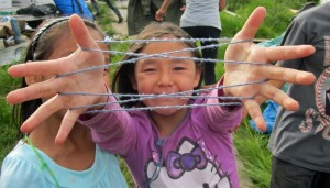Third grader Judith Allen practices string games with friends at the culture camp near Kiana. Photo by Daysha Eaton, KSKA - Anchorage.
