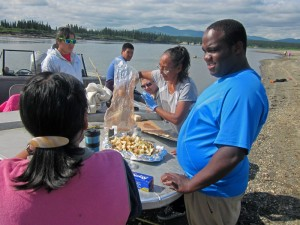 Kevin Foster (right) watches as lunch is prepared during a stop at a beach along the Kobuk River. Photo by Daysha Eaton, KSKA - Anchorage.
