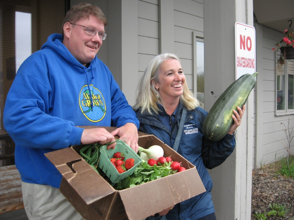 Reps. Bill Stoltze and Cathy Munoz display vegetables grown in Palmer during a legislative tour of Matanuska Valley farms earlier this month. Photo by Ellen Lockyer, KSKA - Anchorage.