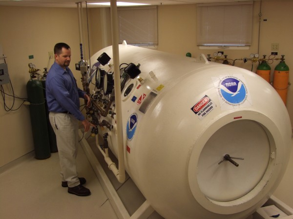 Respiratory therapist Robert Follett stands next to the hyperbaric chamber when it was still in Bartlett Regional Hospital. (Photo courtesy of Jim Strader/Bartlett Regional Hospital)
