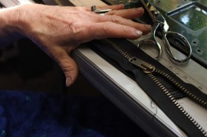 Bridget Milligan works with a zipper in her workshop at the Kodiak Coat Company. Photo by Annie Bartholomew/KTOO