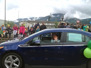 Amy Skilbred parades her electric vehicle on Fourth of July in Juneau.