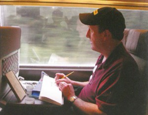 Gurney works while observing the scene out the window of a train.