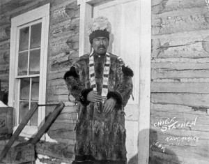 Chief Stephan wearing dentalium bandolier, headdress and ground squirrel parka, Knik, Alaska, c. 1907. Image credit: Anchorage Museum.
