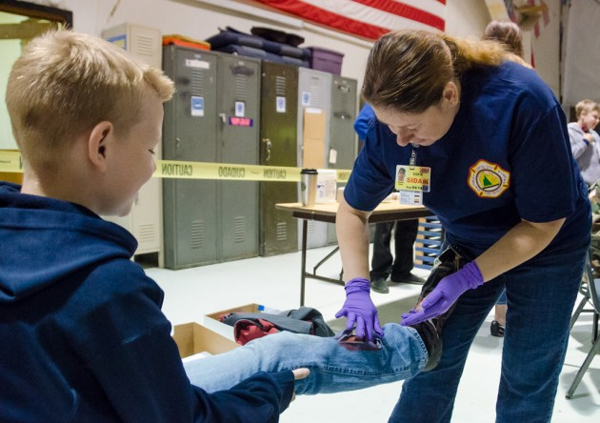 "A young victim gets his leg ""broken."" (Photo by Heather Bryant/KTOO)"