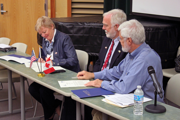 Yukon College president Karen Barnes and UAS chancellor John Pugh sign an agreement renewing the partnership between the two institutions. UAS provost Richard Caulfield oversees the signing. Photo by Lisa Phu - KTOO - Juneau.