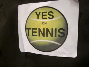 Supporters of building the Northern Lights Recreation Center which would house six indoor tennis courts wore stickers with the words 'Yes on Tennis' scrawled across a green tennis ball at the regular meeting of the Anchorage Assembly Tuesday night.