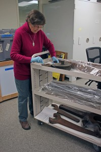 Museum volunteer Fran Dameron affixes numbers onto mining artifacts. Photo by Lisa Phu, KTOO - Juneau.