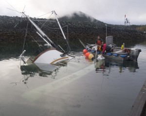 Haines Harbor masters work to cut loose the life raft from the salmon tender Neptune Saturday morning, Oct. 5, 2013 in Haines, Alaska. Photo by John S. Hagen.