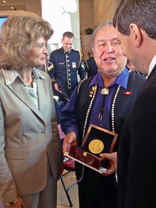 Ozzie Sheakley hold the Congressional Gold Medal awarded to the Tlingit Tribe for code talking service during World War II. He speaks to Sens. Lisa Murkowski and Mark Begich after the ceremony. Photo by Liz Ruskin, APRN - Washington DC.