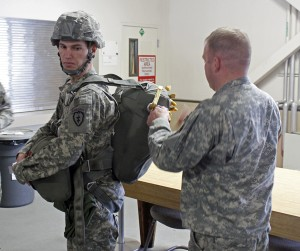 A soldier and jump master demonstrate how to put on a parachute. Photo by Josh Edge, APRN - Anchorage.