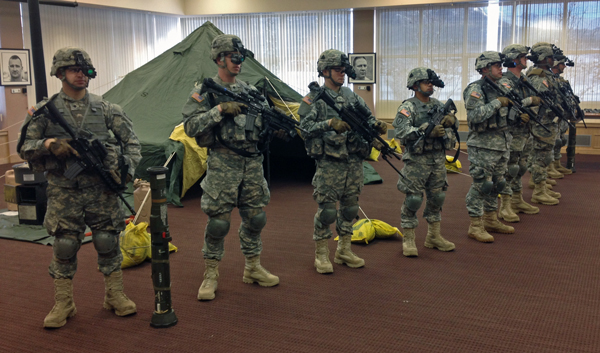 A squad demonstrates the gear they carry into battle. Photo by Josh Edge, APRN - Anchorage.