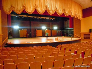 Jeanne on stage at AHS auditorium in 2010 after restoration, but with original flooring.