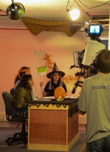 Jade Kalk as a gypsy, Mirriam Meredith as a hippie, and Meghna Bathija as witch sit around the JDTV News anchor desk. Kyle Short is on camera. (Photo by Jeremy Hsieh/ KTOO)