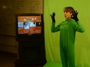 Freshman Jessie Gregg tests a green screen effect for the Halloween episode of JDTV News. The monitor shows what viewers are supposed to see. (Photo by Jeremy Hsieh/ KTOO)