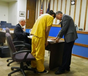 William Buxton signs and places his fingerprint on a document following his sentencing hearing Thursday in Ketchikan Superior Court. Also standing is District Attorney Steve West. Seated is defense attorney Sam McQuerry,