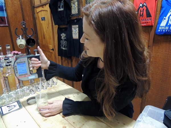 High Mark Distillery owner Felicia Keith-Jones tests the proof on a jar of Blind Cat moonshine at the tasting room in Sterling. Photo by Shaylon Cochran,KDLL - Kenai.