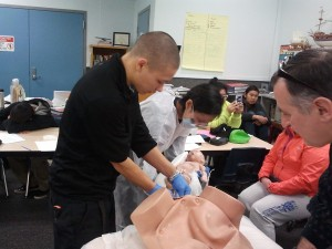 ETT instructor Ron Bowers watches as David Roehl and Kaylene Chuckwak practice emergency obstetrics on a manikin. Photo from KDLG.