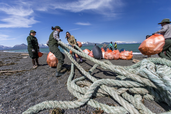 Gyre expedition crew members and National Park Service staff prepare to load marine debris onto a boat during an intensive cleanup of Hallo Bay in Alaska's Katmai National Park, June 2013. Like most of Alaska's 6,640 miles of coastline, Hallo Bay is off the road system, so beach cleanup can only be done by boat charter. This is often prohibitively expensive. Photo by Kip Evans.