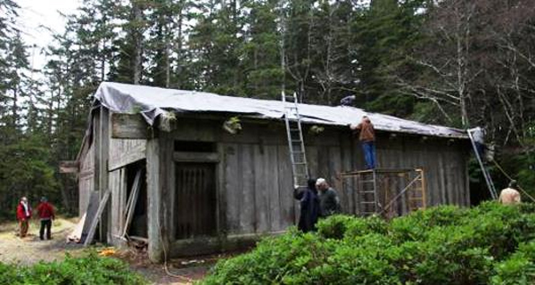 The roof of Kasaan's Chief Son-i-Hat House, also known as the Whale House, is covered by a tarp during repair work. (Organized Village of Kasaan.)