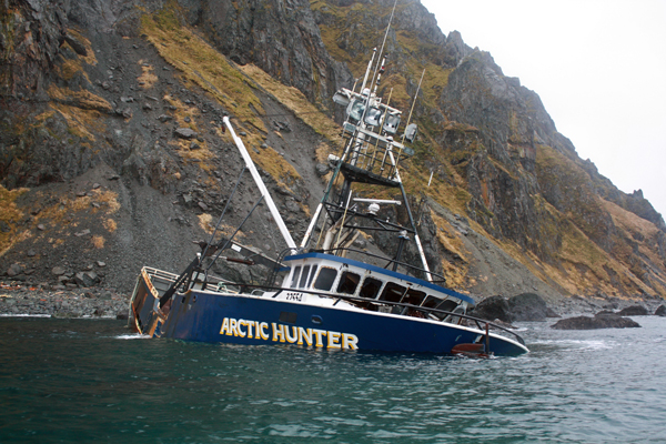 Dan Magone on the deck of the Arctic Hunter, with debris visible on the beach. Photo by Annie Ropeik, KUCB - Unalaska.