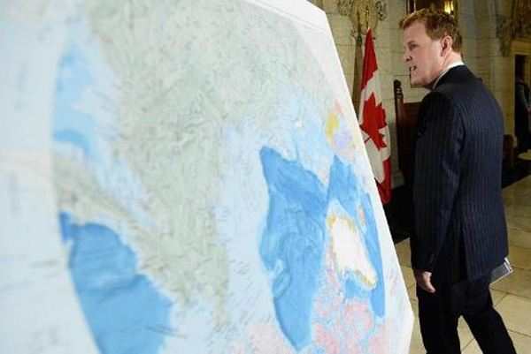 Foreign Affairs Minister John Baird walks past a map of the Arctic at a news conference on Canada's Arctic claim in Ottawa, on Dec 9 2013. Photo by Sean Kilpatrick, The Canadian Press.