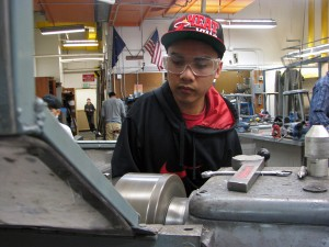 Mark Partido operates a metal lathe in the school's metal shop. Photo by Robert Woolsey, KCAW - Sitka.
