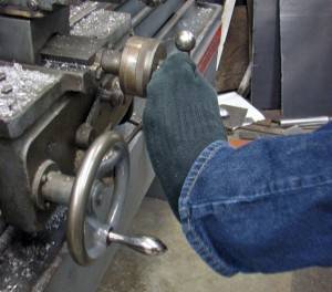 Mark Partido was born with arthrogryposis, which limits the use of his lower arms and hands, so he operates the lathe with his toes. Photo by Robert Woolsey, KCAW - Sitka.