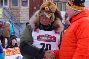 Receiving congratulations from Iditarod Trail Committee Executive Director Stan Hooley. KNOM Photo.